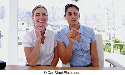 Businesswomen using a non-visible interface in their office