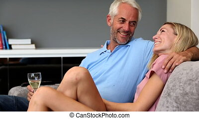 Mature couple talking each other on a sofa with a glass of...