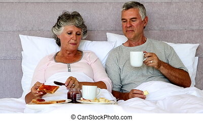 Mature couple enjoying breakfast in bed with fruits and jam
