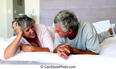 Mature couple talking each other on the bed lying on their...