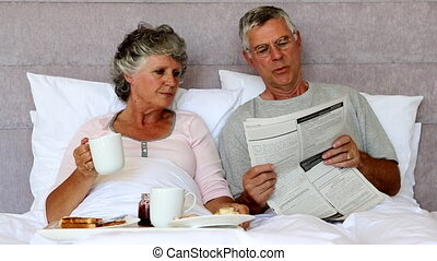 Husband reading the newspaper to his wife during breakfast...