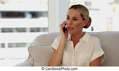 Blonde businesswoman on the phone sat on a sofa