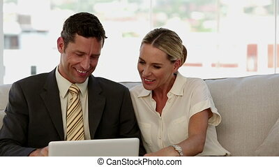 Laughing colleagues looking at a laptop and sat on a sofa