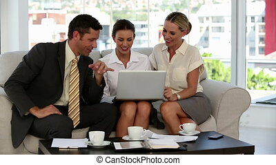 Business people working on a laptop while they are sat on a...