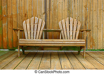 A dual wooden seat with a center table on a wooden deckpatio...