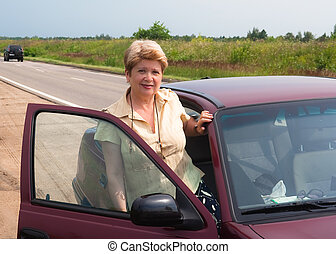 A woman sits in the car