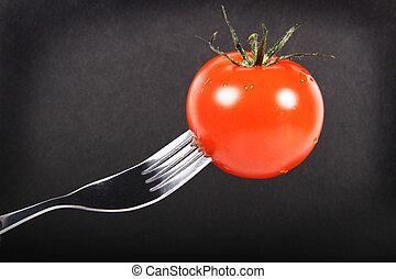 fresh plumb tomatoe on a fork - fresh round tomatoe on a...