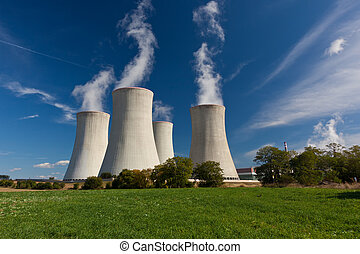 Cooling towers - Steaming cooling towers on green meadow