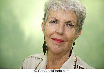Portrait of old caucasian lady looking and smiling at camera