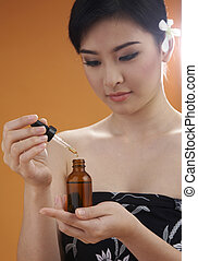 young woman blending aroma oil