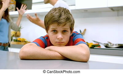 Sad boy with arms folded while parents quarreling in slow...
