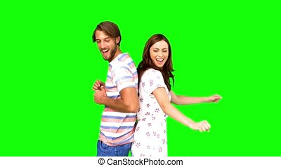 Friends dancing back to back on green screen in slow motion