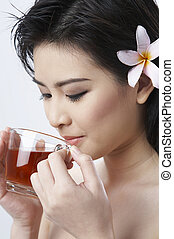 woman drinking hot ginger tea - A woman with a flower in her...