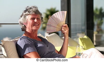 Woman fanning herself on the balcon - Mature woman feeling...
