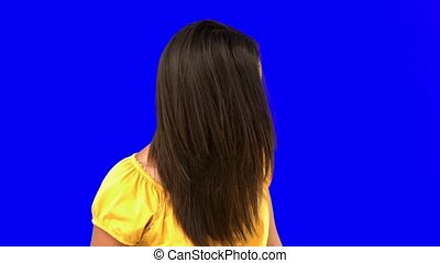 Smiling woman tossing her hair on blue screen in slow motion