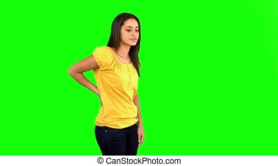 Woman rubbing painful back on green screen in slow motion
