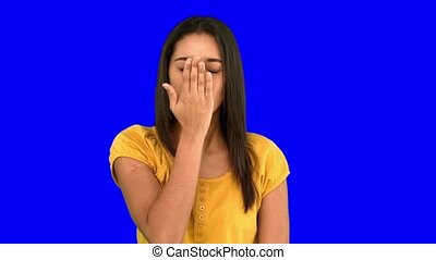 Woman blowing a kiss on blue screen in slow motion