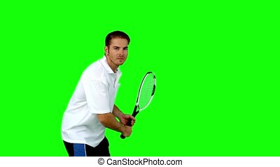 Attractive man playing tennis in slow motion on green screen...