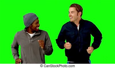 Two men running on green screen in slow motion on green...