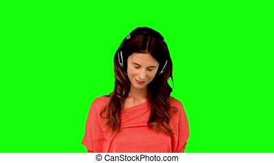 Woman with headphone listening to music on green screen in...