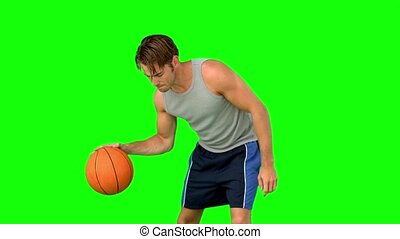 Man training at basketball in slow motion on green screen
