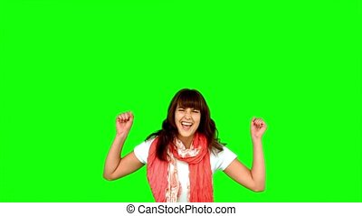 Brunette woman jumping on green scr