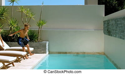 Brother and sister diving into the swimming pool in slow...