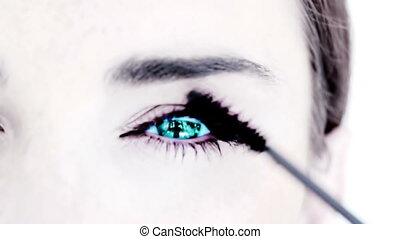 Blue eyed woman making up with mascara against white...