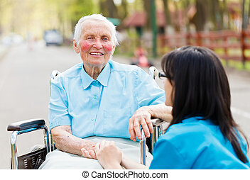 Nurse Consoling Senior Patient - Kind elderly lady sitting...