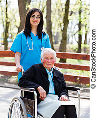 Walking With Senior Patient In Wheelchair - Kind doctor,...