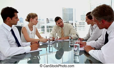 Angry businessman yelling at employees during a meeting in...