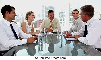 Laughing businessman giving thumbs up with colleagues around...