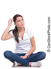 casual woman sits puzzled - casual young woman sitting with...
