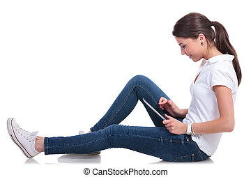 casual woman on floor with tablet - side view of a casual...