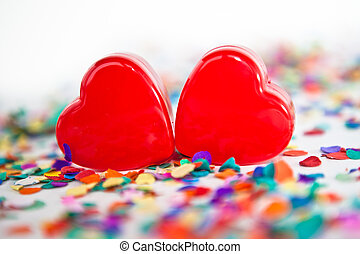 Two red hearts with confetti