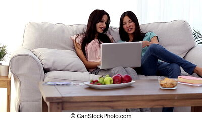 Friends using laptop together - Attractive friends using...
