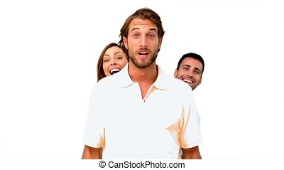 Friends hiding behind a man on white background in slow...