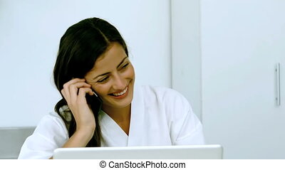 Woman laughing during a phone conversation with a laptop in...