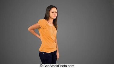 Woman rubbing painful back on grey background in slow motion