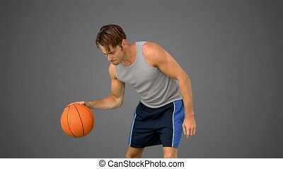 Man training at basketball in slow motion on grey background