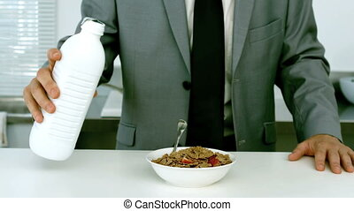 Well dressed businessman pouring milk into his cereals for...