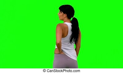 Woman in sportswear turning against green screen in slow...