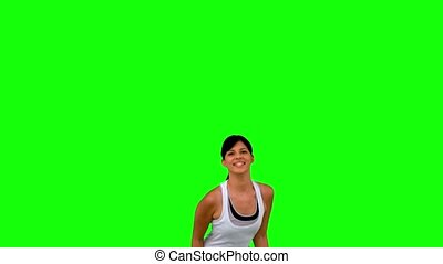 Woman in sportswear jumping on green screen in slow motion