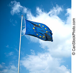 European Union flag floats in the air with clouds and blue...