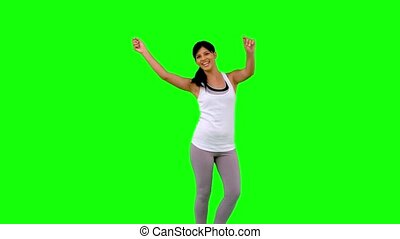 Woman in sportswear dancing on green screen  in slow motion