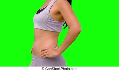 Athletic woman turning to camera against green screen in...