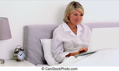 Mature woman using laptop in her bedroom then smiling at...