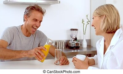 Cheerful man pouring orange juice in slow motion