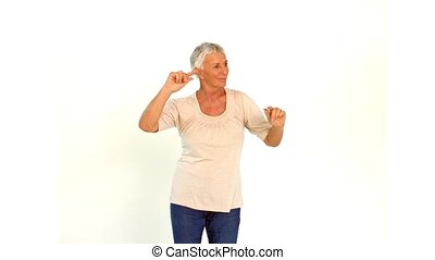 Senior woman dancing against white background in slow motion