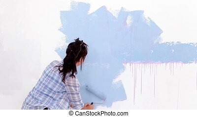 Attractive woman painting her wall